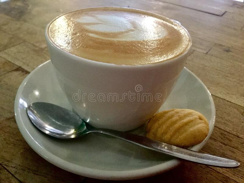 Coffee and cookie on Wooden table. Classic cappuccino . stock photos