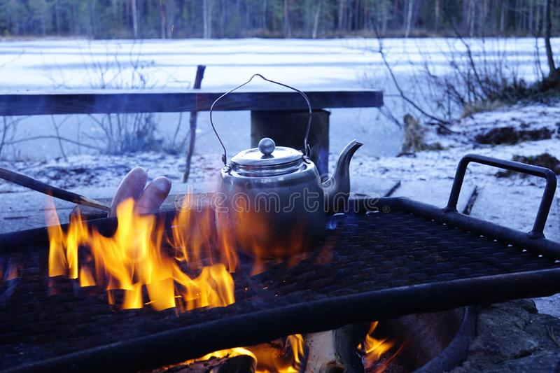 Coffee cooking on open fire. Open fire in nature. Roasting sausages and cooking coffee in nature royalty free stock images