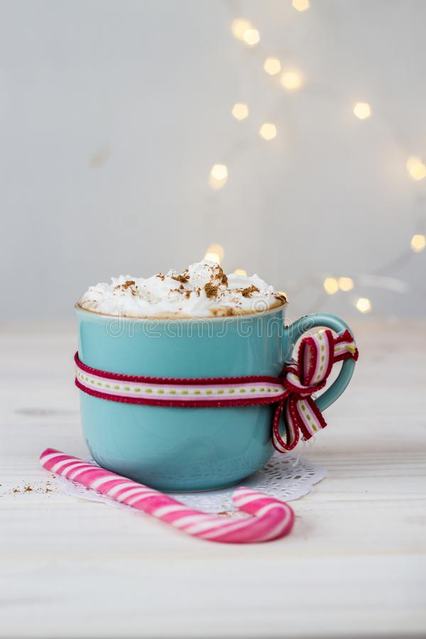Coffee with cream in a ceramic mug with a ribbon and christmas candy on bokeh background royalty free stock photography