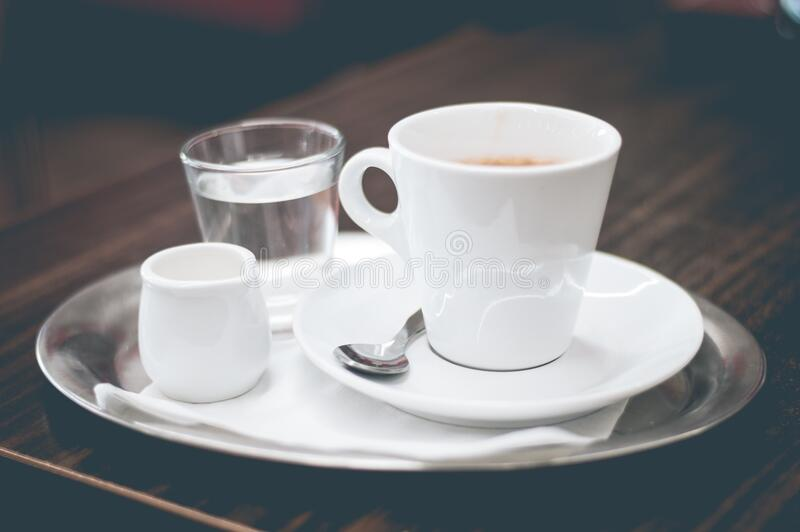 Coffee, cream and water on silver tray stock photo