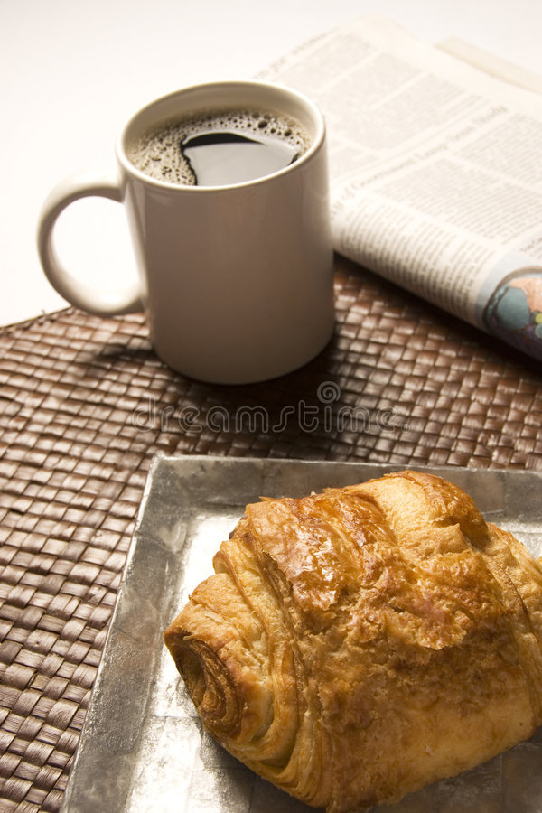 Coffee and croissant. Morning coffee, pastry, and newspaper royalty free stock photography