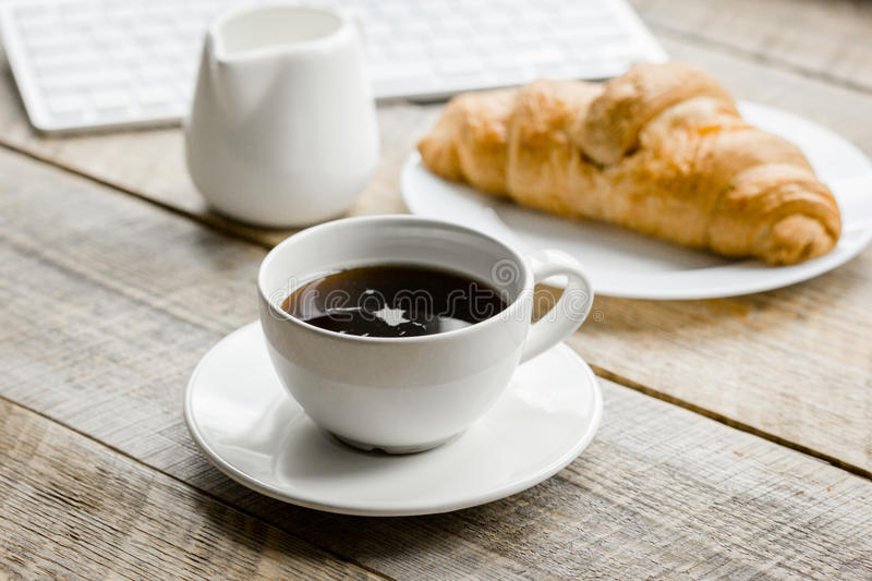 coffee and croissant for breakfast of businessman wooden office desk background royalty free stock images
