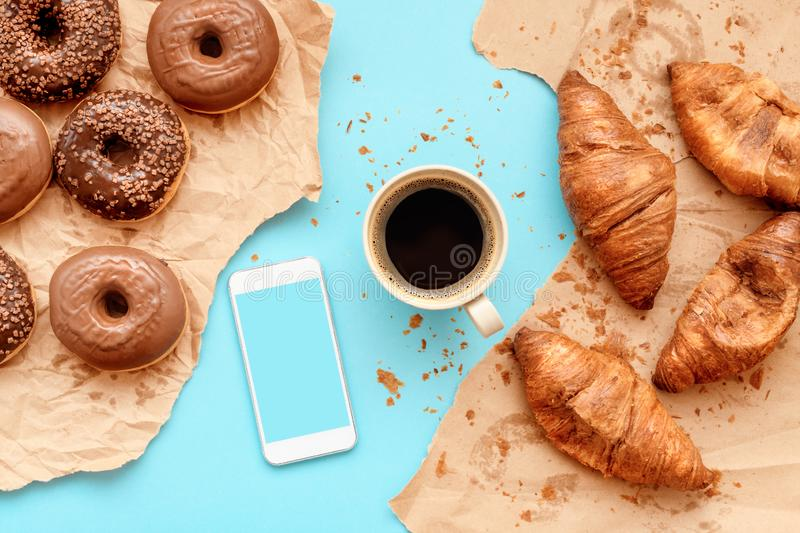 Coffee croissants and chocolate doughnuts with smart phone mock up royalty free stock photos