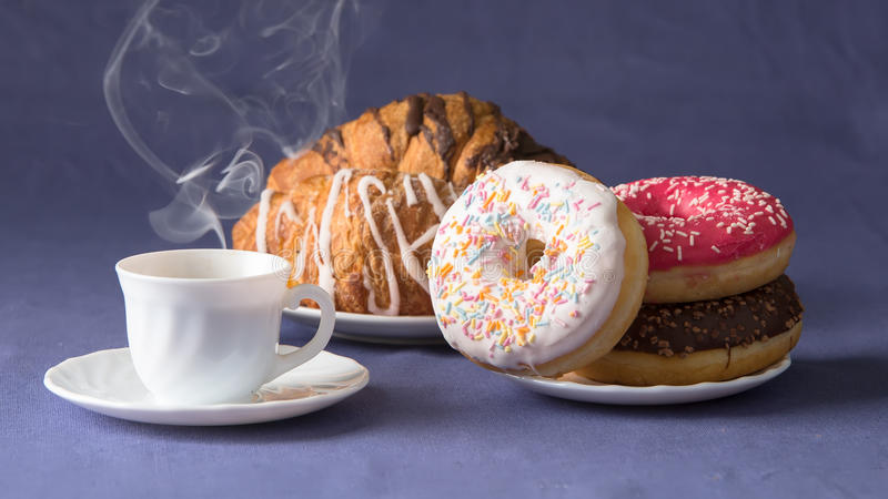 Coffee with croissants and donuts. Cup of coffee with croissants and donuts royalty free stock image