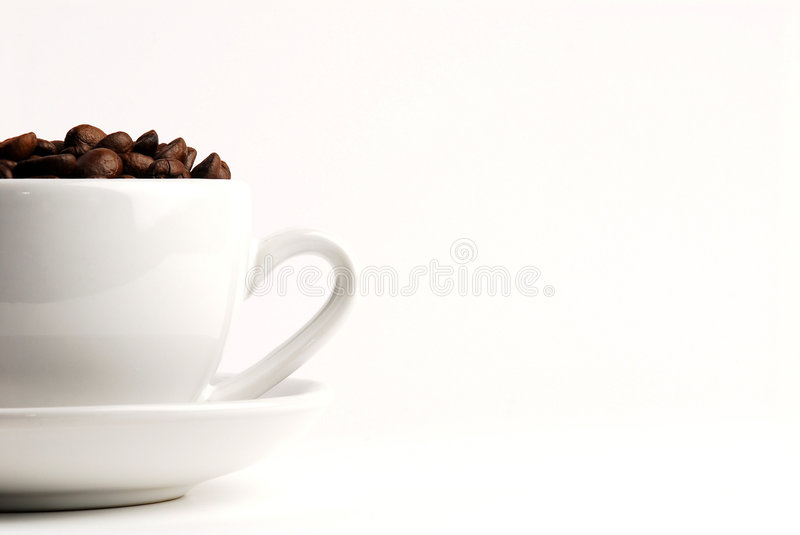 Coffee cup 2. Cappuccino cup and saucer filled with coffee beans. Shot white on white for a clean look, and to highlight the rich colour of the beans. Shallow stock photos