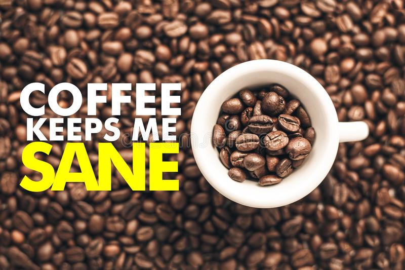 Coffee cup on background with message `COFFEE KEEPS ME SANE`. Coffee cup is seen from the top on a background made of coffee beans and with message `COFFEE KEEPS royalty free stock photo