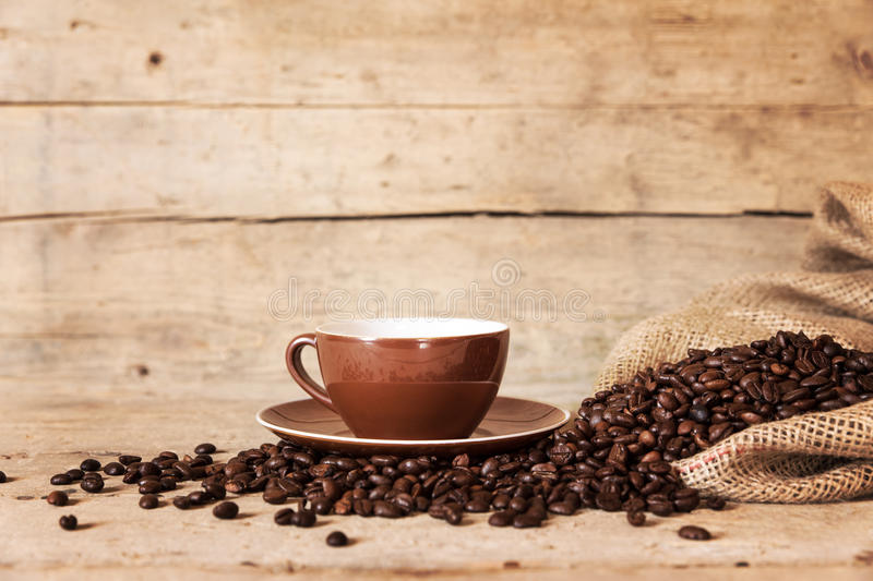 Coffee cup, beans and a burlap bag on old wooden background stock photo