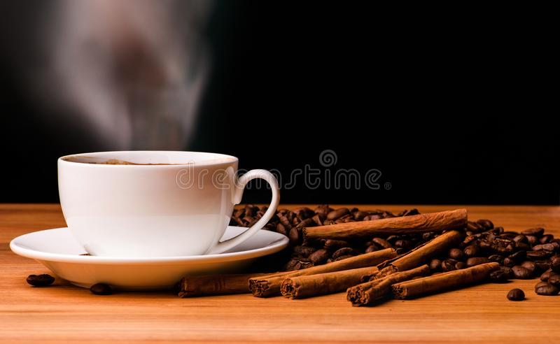 Coffee cup, coffee beans and cinnamon sticks on dark background stock images