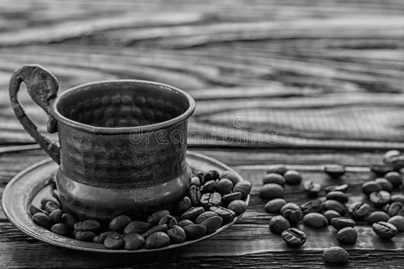 A coffee cup with coffee beans on an old wooden table. Fried coffee beans on a wooden background.  Black and white image.Viewing royalty free stock images