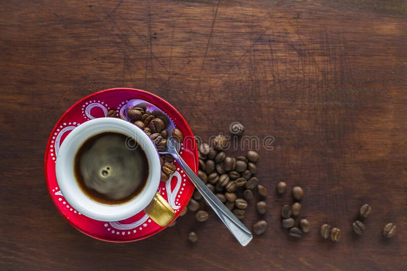 coffee cup with beans spoon against wood stock photos