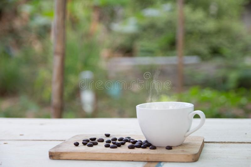 Coffee cup and coffee beans on table. Snacks, cookies with coffee cups and coffee beans on the desk with natural light in the morning stock photography