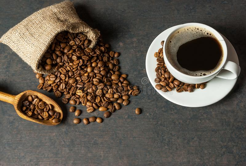 Coffee cup and beans with wooden shovel or spoon and stack of beans in burlap sack, on black rustic vintage table, Coffee concept stock photos