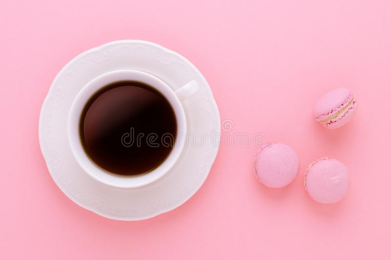 Coffee cup black with handmade macaroons on pink background from above stock photo