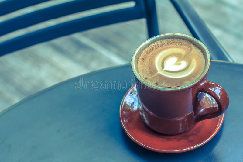 Coffee cup on black metal table in coffee shop. stock images