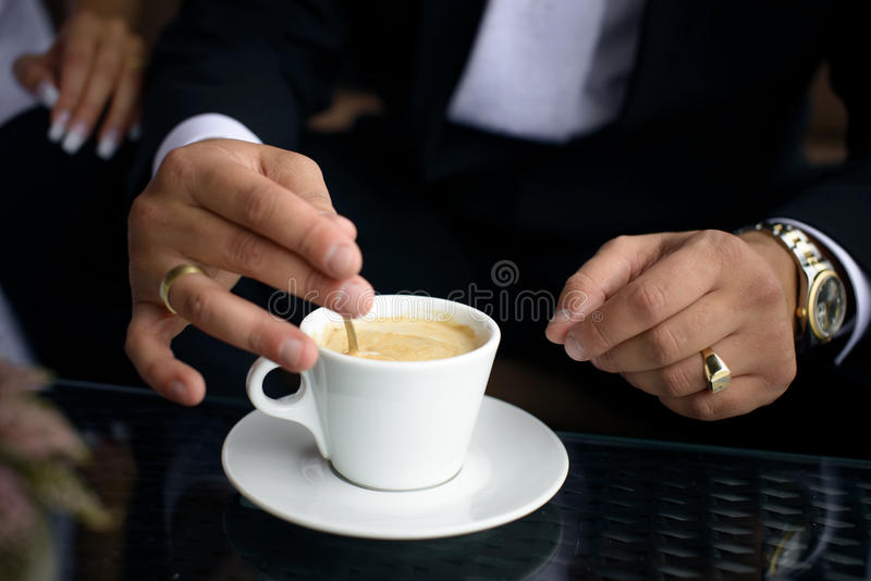 Coffee cup on a black table. Businessman holding coffee cup stock image