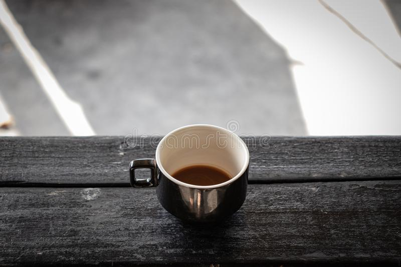Coffee cup on a black wood table, outside royalty free stock images