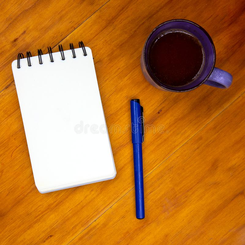 Coffee cup and blank page of notepad with pen on wooden table. White paper notebook top view photo stock images