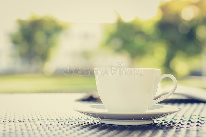 Coffee cup with book on blurred green nature background royalty free stock photos