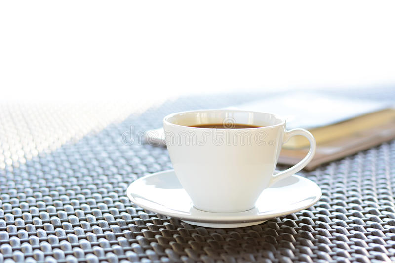 Coffee cup with book on wicker table royalty free stock photography