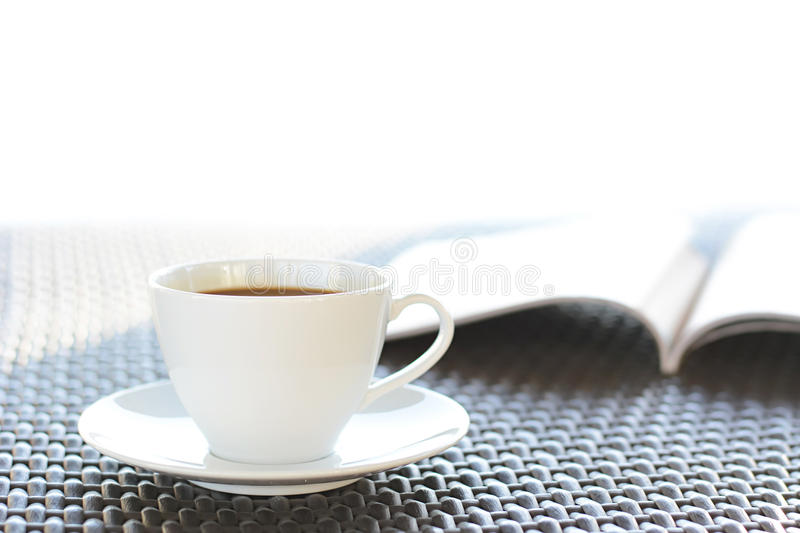 Coffee cup with book on wicker table royalty free stock photos