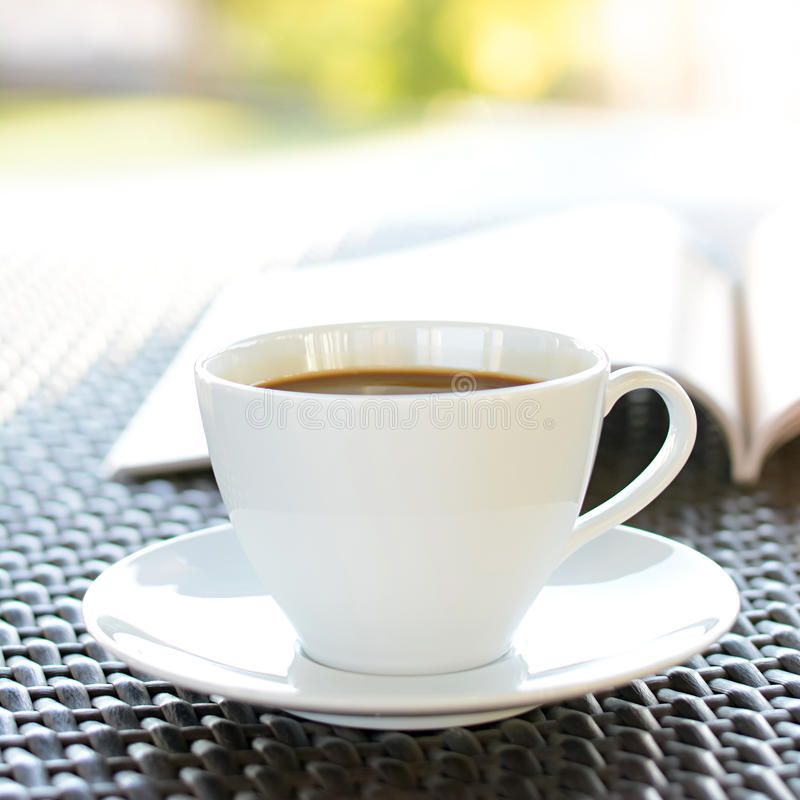 Coffee cup with book on wicker table stock photo