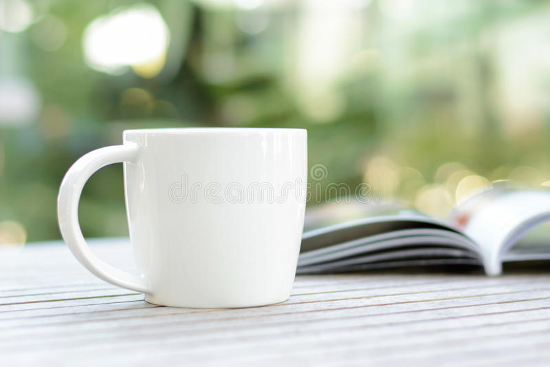 Coffee cup with book on wood table with blur bokeh background stock photo