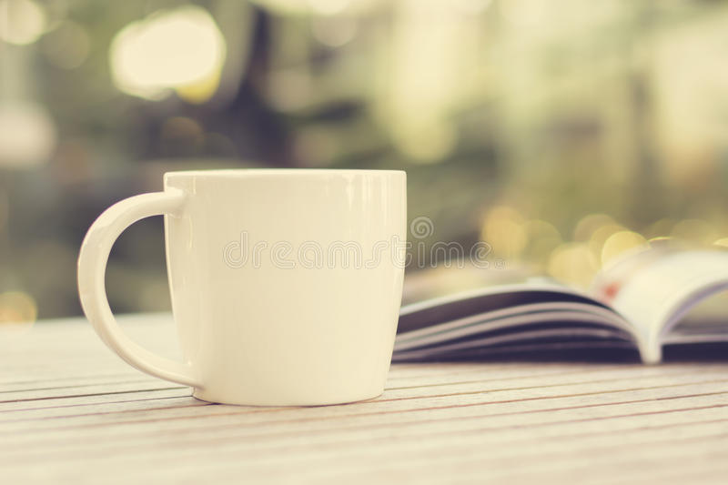 Coffee cup & book on wood table stock image