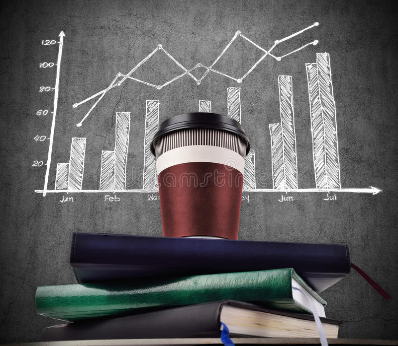 Coffee cup on books and drawing stock chart. Disposable coffee cup on books and drawing stock chart on wall stock image
