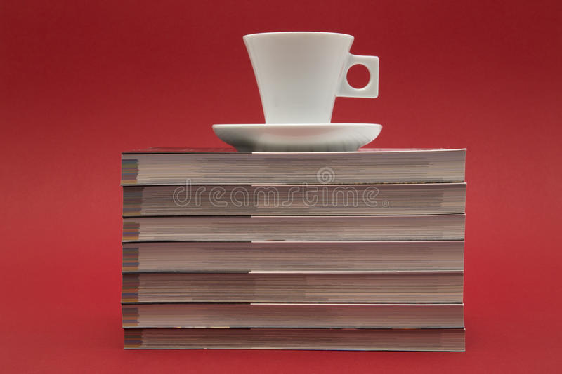 Coffee cup and books. A coffee cup and seven books on a red background stock images