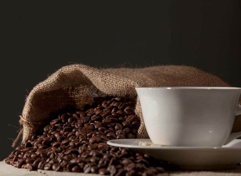 Coffee cup with burlap sack of roasted beans against dark wood b royalty free stock image