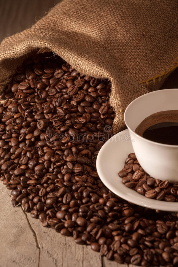 Coffee cup with burlap sack of roasted beans stock photo