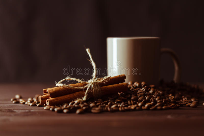 Coffee cup with burlap sack of roasted beans on rustic table stock photography