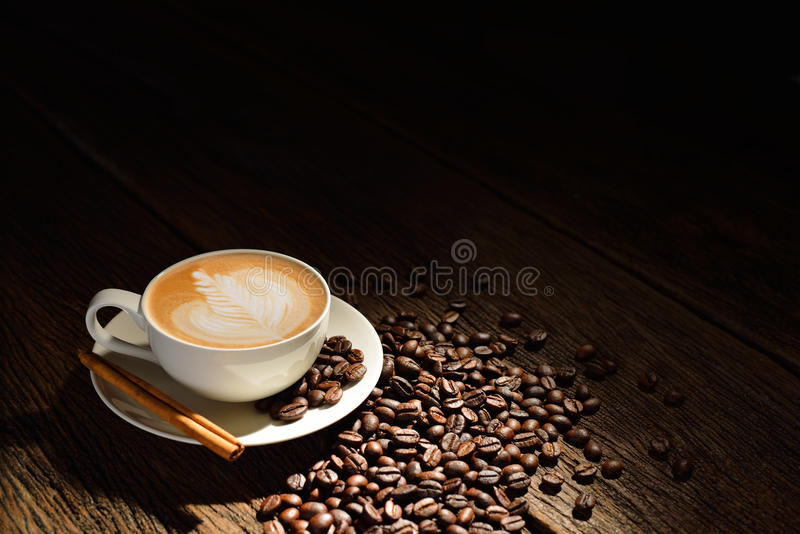Coffee. Cup of cafe latte and coffee beans on old wooden background royalty free stock photo