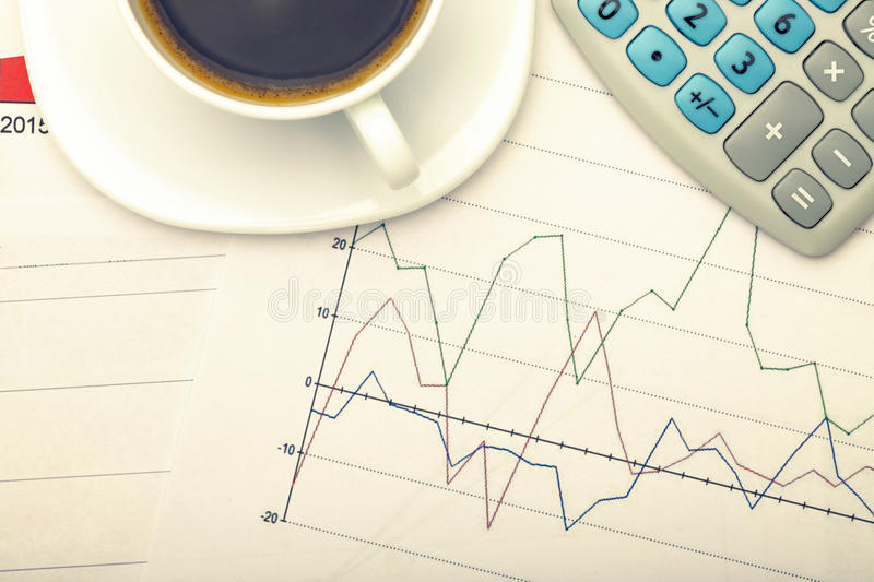Coffee cup and calculator over financial charts. Filtered image: cross processed vintage effect. stock photos