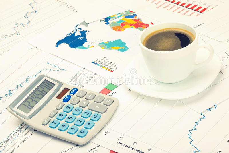 Coffee cup and calculator over financial charts - studio shot. Filtered image: cross processed vintage effect. stock photos