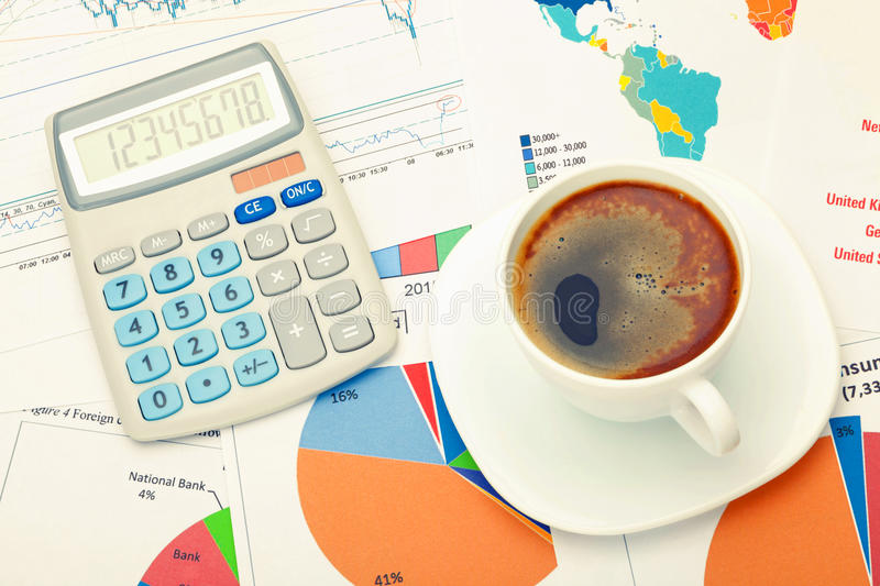 Coffee cup and calculator over financial documents - studio shot. Filtered image: cross processed vintage effect. royalty free stock image