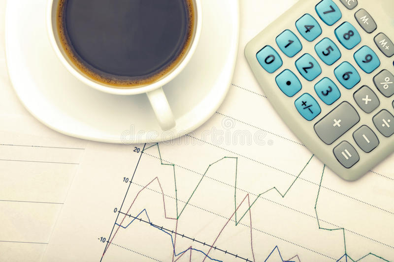 Coffee cup and calculator over stock market charts - view from top. Filtered image: cross processed vintage effect. royalty free stock image