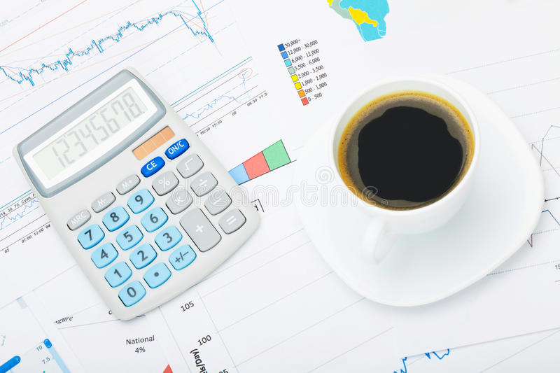 Coffee cup and calculator over world map and some financial documentation - close up studio shot stock photo