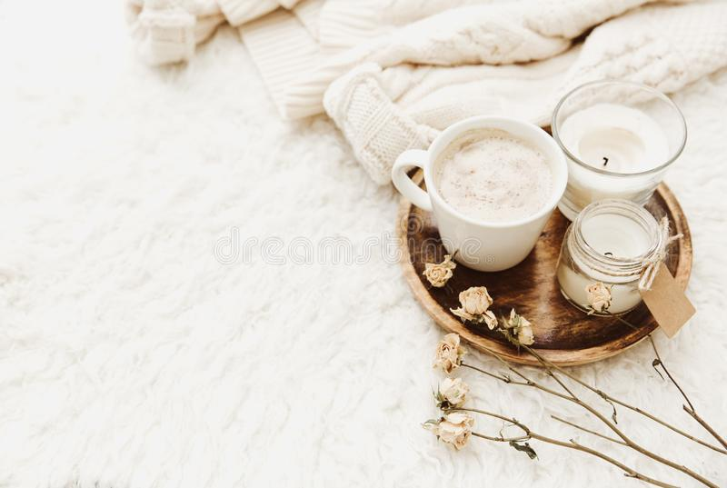 Coffee cup with candles in cozy home atmosphere. Warm sweater stock images