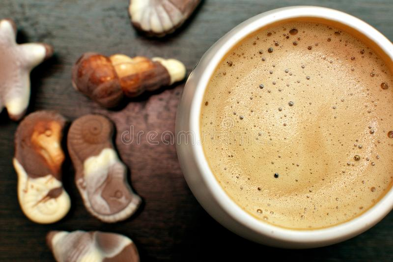 Coffee cup, cappuccino and gourmet Belgian chocolate on a wooden table stock photo