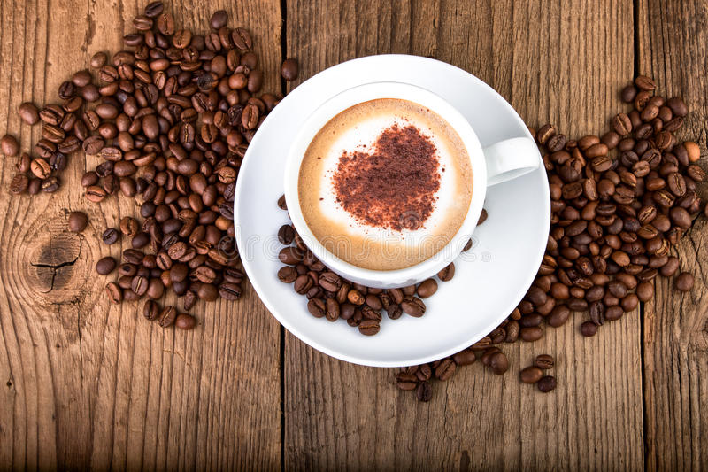 Coffee cup Cappuccino on old wooden table. Heart shape foam, top view stock photo
