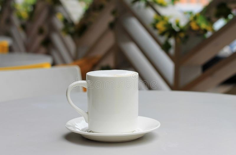 Coffee cup with cappuccino on a table in a cafe. Close-up, plase for text. White coffee cup with cappuccino on a table in a cafe. Close-up, plase for text stock image