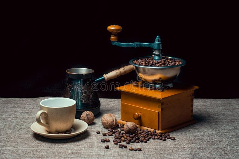 Coffee cup with a cezve and coffee grinder with coffee beans and nuts on a dark background stock photo