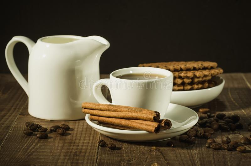 Coffee cup with cinnamon, creamer and chocolate cookies/coffee c. Up with cinnamon, creamer and chocolate cookies on a wooden background. selective focus stock photo