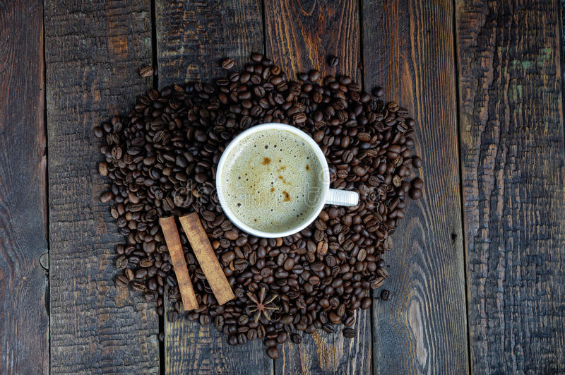 Coffee cup with cinnamon sticks and anis star on old rustic table. Top view. Wood background stock images