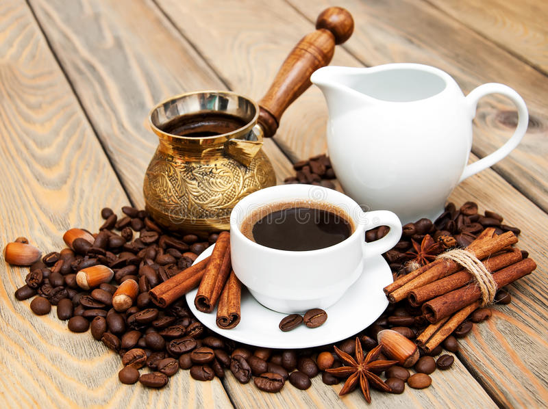 Coffee cup with coffee beans, milk jug and turk on a wooden b stock photos