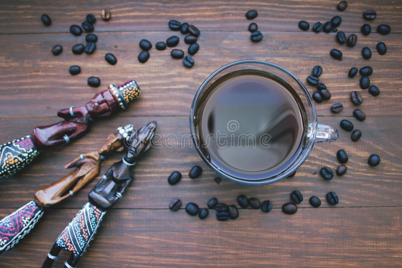 Coffee Cup, coffee beans and wooden African statues. The concept of traveling to Africa royalty free stock image