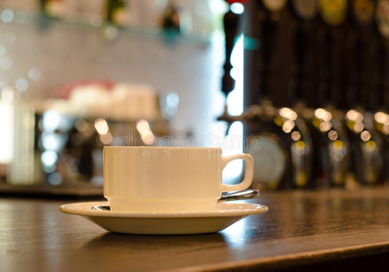Coffee cup on a counter in a bar. Coffee cup and saucer standing on a wooden counter in a bar with a view to the beer taps in the background royalty free stock images