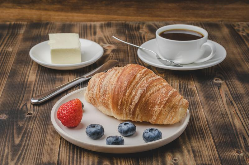 Coffee cup, croissant with berries in white bowl and butter knife on wooden table. Selective focus. Healthy breakfast with fresh stock photos
