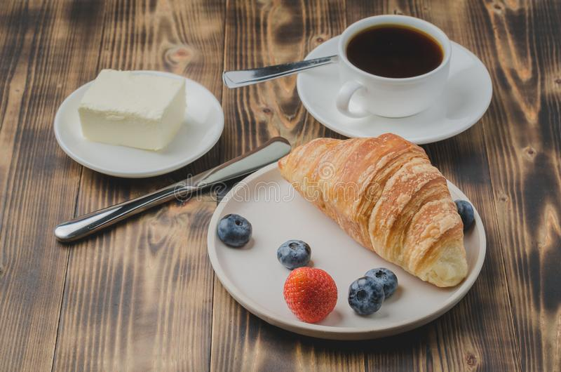 Coffee cup, croissant with berries in white bowl and butter on wooden background. Healthy breakfast with fresh berries stock photography